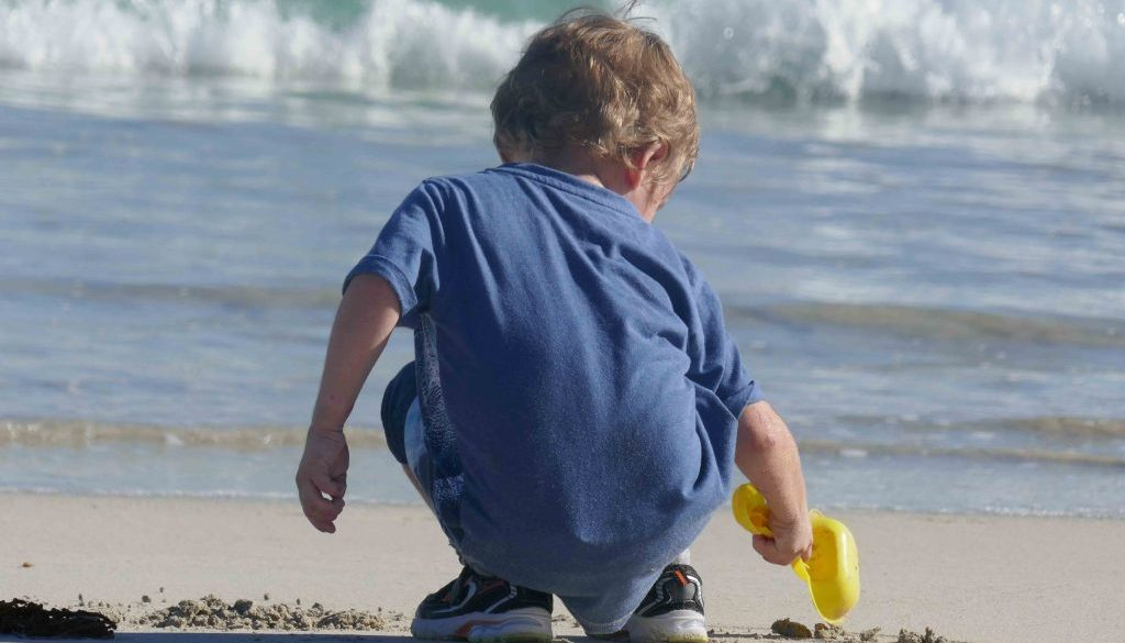 https://www.writteninwaikiki.com/10-tips-taking-better-photos-kids/ child beach digging in the sand