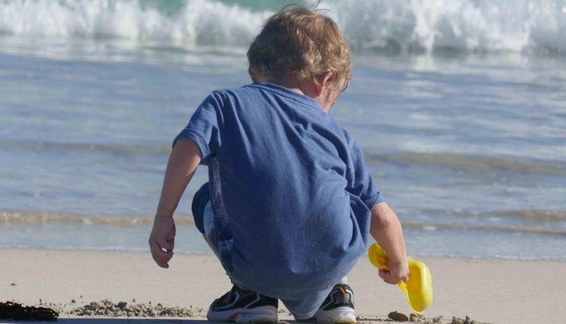 https://www.writteninwaikiki.com/10-tips-taking-better-photos-kids/ child beach digging in the sand