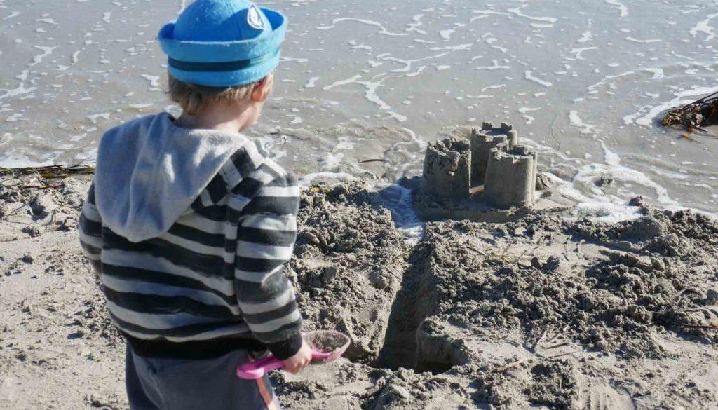 https://www.writteninwaikiki.com/why-i-started-this-blog/ kids playing in sand at the beach Waikiki Rockingham Western Australia