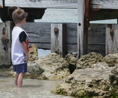 how to build self-esteem in kids child boy at beach staring at bridge