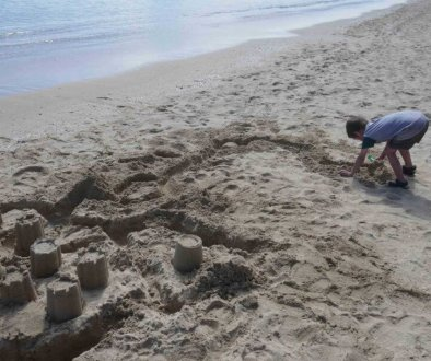 why being bored is good for kids. Boy building sandcastles at the beach
